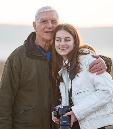 Older man with arm around granddaughter