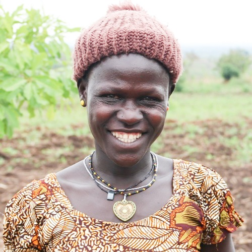 Woman in knit hat smiling on camera.